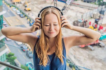 Una mujer joven junto a la ventana molesta por el edificio trabaja afuera, con auriculares inalámbricos insonorizados con cable.