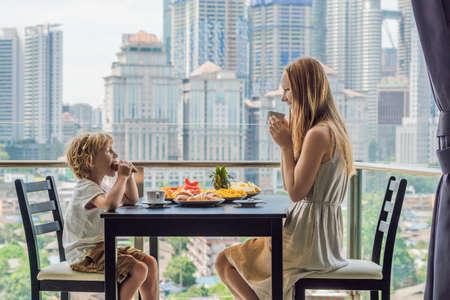 Ontbijten op het balkon en gelukkige familie. Ontbijttafel met koffiefruit en broodcroisant op een balkon tegen de achtergrond van de grote stad. Stockfoto