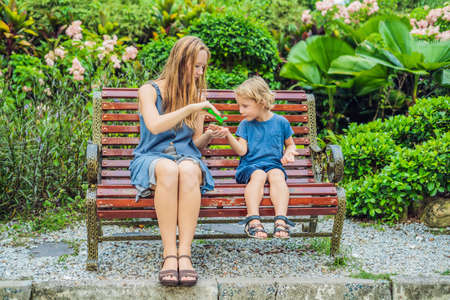 Mother and son using wash hand sanitizer gel in the park before a snack. Stock Photo