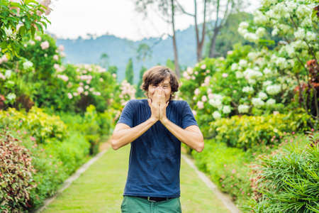 Young man sneeze in the park against the background of a flowering tree. Allergy to pollen concept. Stock Photo