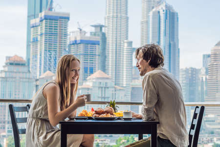 Loving couple having breakfast on the balcony. Breakfast table with coffee fruit and bread croisant on a balcony against the backdrop of the big city.