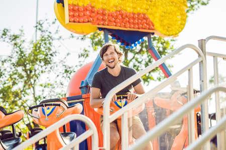 Beautiful, young man having fun at an amusement park. Stock Photo