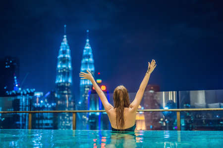 Young woman in outdoor swimming pool with city view at night.