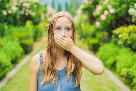 Young woman sneezes in the park against the background of a flowering tree. Allergy to pollen concept.