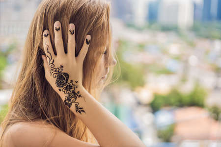 Portrait of a young indian woman in casual style with mehendi against the background of a big city. Malaysia Banque d'images