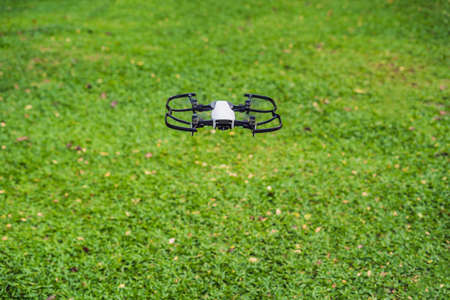 White drone flying against the grass background.