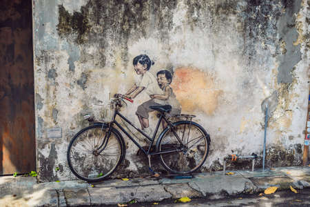 Georgetown, Penang, Malaysia - April 20, 2018: Public street art Name Children on a bicycle painted 3D on the wall thats two little Chinese girls riding bicycle in Georgetown, Penang, Malaysia
