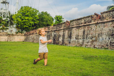 Boy on background of Fort Cornwallis in Georgetown, Penang, is a star fort built by the British East India Company in the late 18th century, it is the largest standing fort in Malaysia. Traveling with children concept.