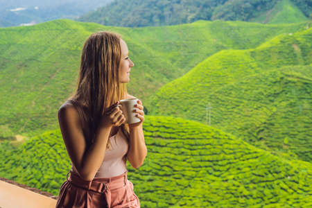 Young woman Drinking Healthy Green Tea against a tea plantation. Healthcare or Herbal medicine concept.