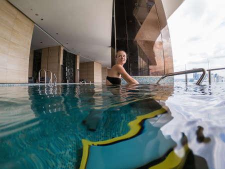 Giovane donna sul simulatore di biciclette sott'acqua in piscina.