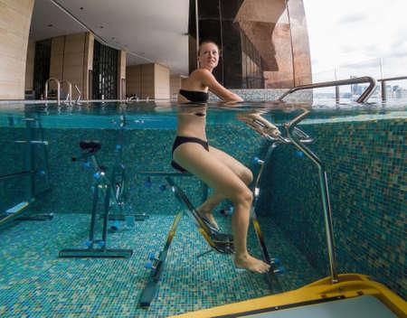 Giovane donna sul simulatore di biciclette sott'acqua in piscina. Archivio Fotografico