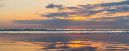 Panorama, Banner, long format of Sunset on the Kuta beach with reflection in the water on the island of Bali.