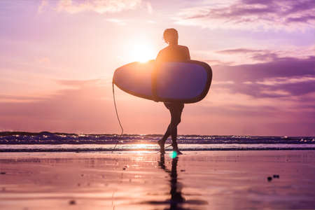 Vacation Silhouette Of A Surfer Carrying His Surf Board Home At Sunset With Copy Space.