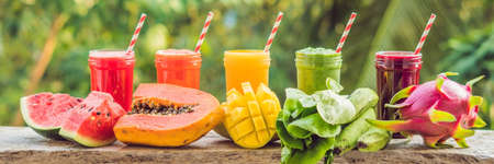 Rainbow from smoothies. Watermelon, papaya, mango, spinach and dragon fruit. Smoothies, juices, beverages, drinks variety with fresh fruits on a wooden table. BANNER, long format