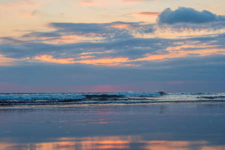 Sunset on the Kuta beach with reflection in the water on the island of Bali. Stock Photo