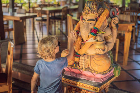 Caucasian boy high-five Ganesha. Meeting Western and Eastern culture concept. oriental and occidental. Traveling to Asia with children.
