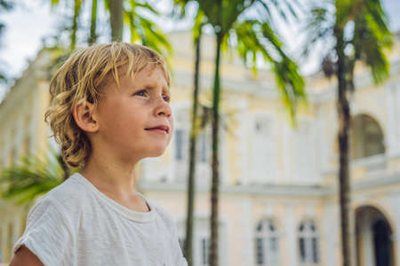 Boy on background of Old Town Hall in George Town in Penang, Malaysia. The foundation stone was laid in 1879. Traveling with children concept. Stock Photo