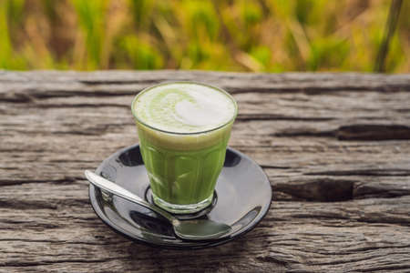 Cup of matcha latte against the old wooden table. Reklamní fotografie