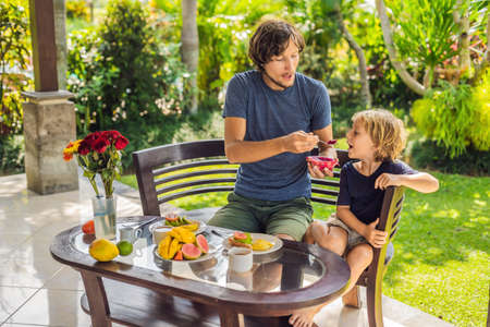 Family of two eating nicely served breakfast outside