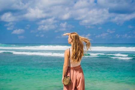 Young woman traveler on amazing Melasti Beach with turquoise water, Bali Island Indonesia.