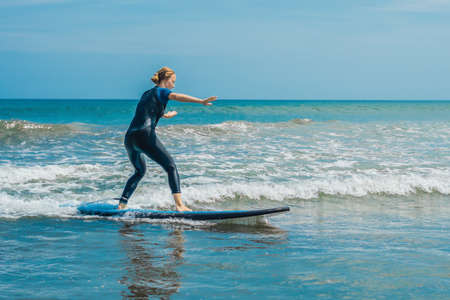 Joyful young woman beginner surfer with blue surf has fun on small sea waves.