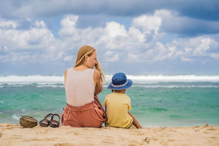 Mom and son travelers on amazing Melasti Beach with turquoise water, Bali Island Indonesia. Traveling with kids concept. Stock Photo