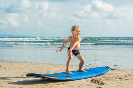 Little boy surfing on tropical beach. Child on surf board on ocean wave.