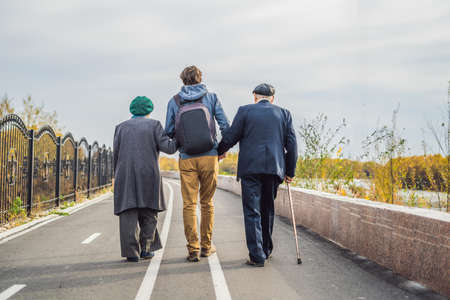 An elderly couple walks in the park with a male assistant or adult grandson.
