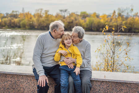 Senior couple with baby grandson in the autumn park. Great-grandmother, great-grandfather and great-grandson.