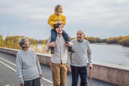 An elderly couple walks in the park with a river with their grandson and great-grandson.