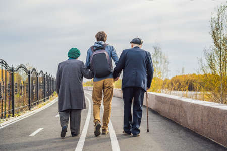 An elderly couple walks in the park with a male assistant or adult grandson. Caring for the elderly, volunteering.