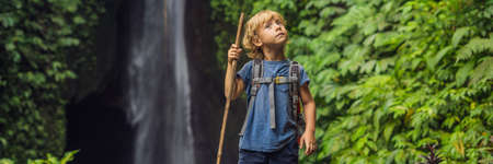 Boy with a trekking stick of Leke Leke waterfall in Bali island Indonesia.