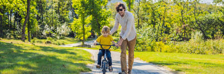 Father teaches his son ride a bicycle. Reklamní fotografie
