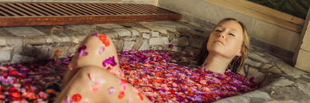 Attractive Young woman in bath with petals of tropical flowers and aroma oils. 写真素材