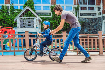 Dad teaches son to ride a bike in the park.