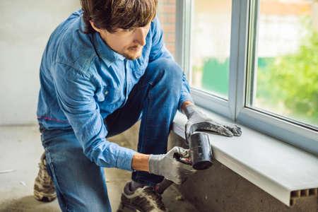 Man in a blue shirt does window installation. Standard-Bild - 112696715