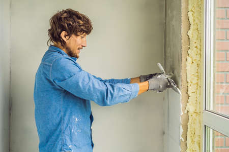 master is applying white putty on a wall and smearing by putty knife in a room of renovating house in daytime. Banque d'images - 112697235