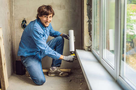 Man in a blue shirt does window installation. Using a mounting foam.