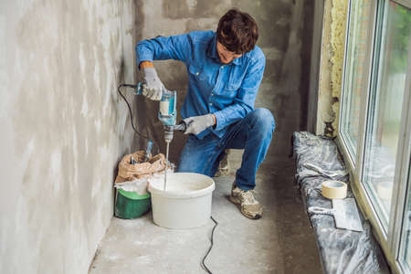 Young male painter kneads putty with water in a bucket using a hand-held mixer for building mixes. Imagens - 112698002