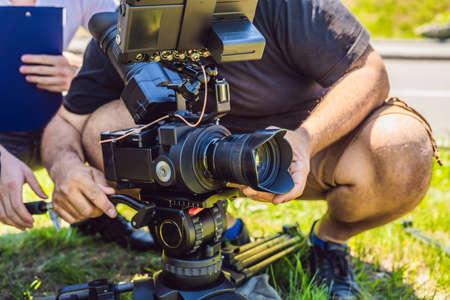 un cameraman professionista prepara una macchina fotografica e un treppiede prima delle riprese. Archivio Fotografico