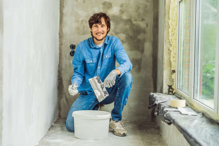 master is applying white putty on a wall and smearing by putty knife in a room of renovating house in daytime.