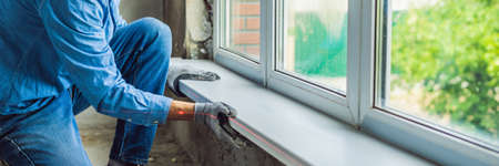 Man in a blue shirt does window installation. BANNER, long format
