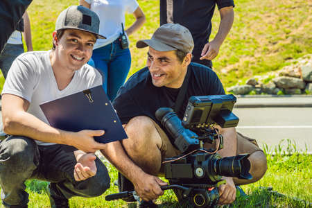 A cameraman operator discuss the shooting process with a director and dp