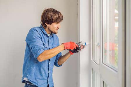 Man in a blue shirt does window installation. Standard-Bild - 113813724