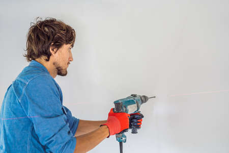A man makes a hole in the wall with a drill.