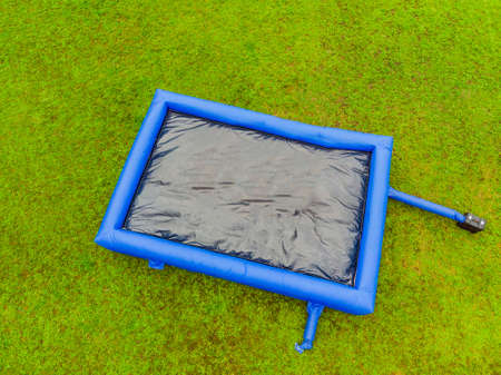 Big inflatable blue trampoline on green grass.