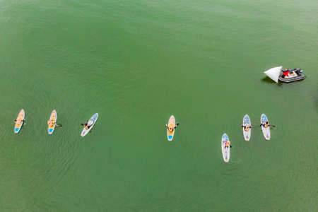 Strong men floating on a SUP boards in a beautiful bay on a sunny day. Aerial view of the men crosses the bay using the paddleboard. Water sports, competitions.