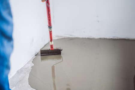 plâtrier pendant les travaux de revêtement de sol avec du mortier de ciment autonivelant.