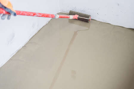 plasterer during floor covering works with self-levelling cement mortar.
