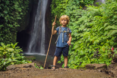 Boy with a trekking stick on the background of Leke Leke waterfall in Bali island Indonesia. Traveling with children concept.